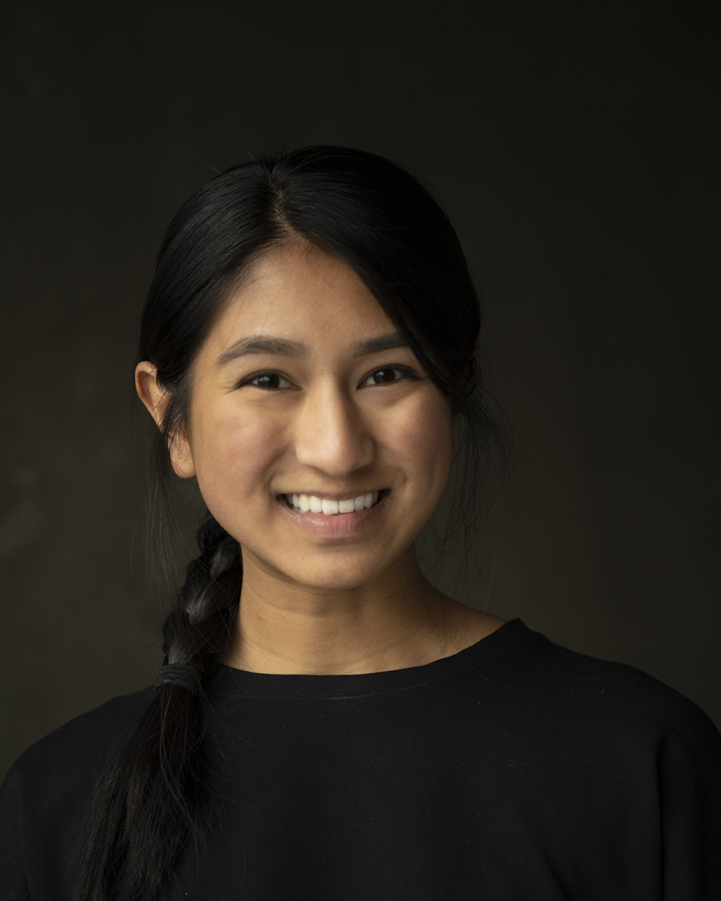 A person with a long black braid smiling in front of a black background
