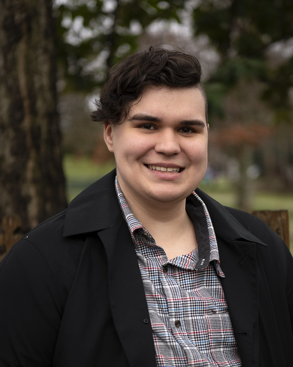 A person in a coat and a plaid shirt smiling in front of a park