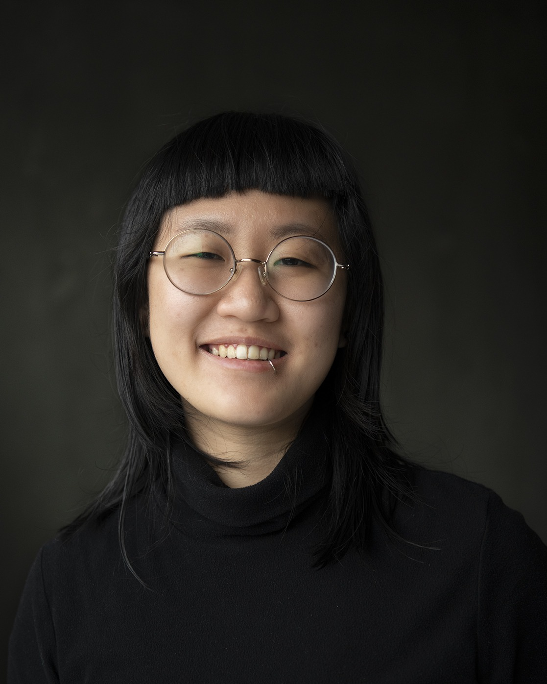 A person with short bangs and glasses smiling in front of a black background