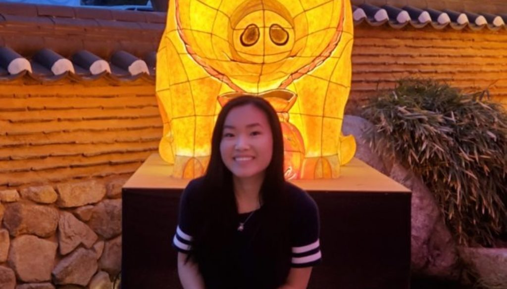 A person sitting with their legs crossed in front of a glowing pig lantern