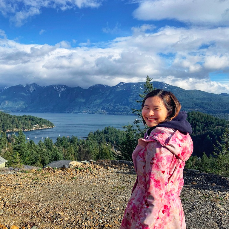 A person in a pink jacket in front of a mountain and lake view,looking over their shoulder