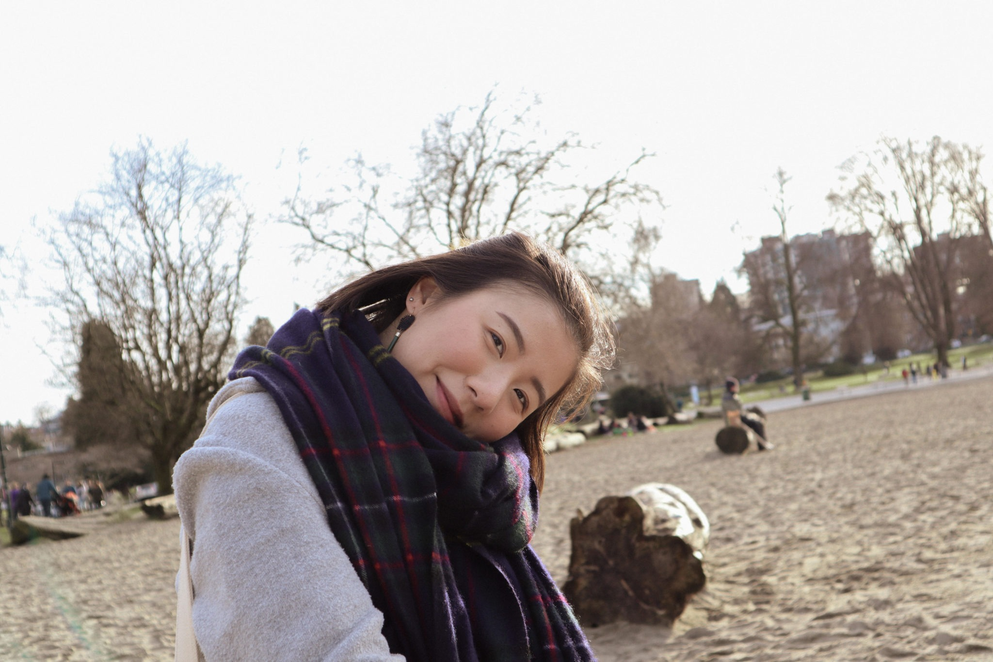 A person in a plaid scarf on a winter beach smiling with their head angled sideways