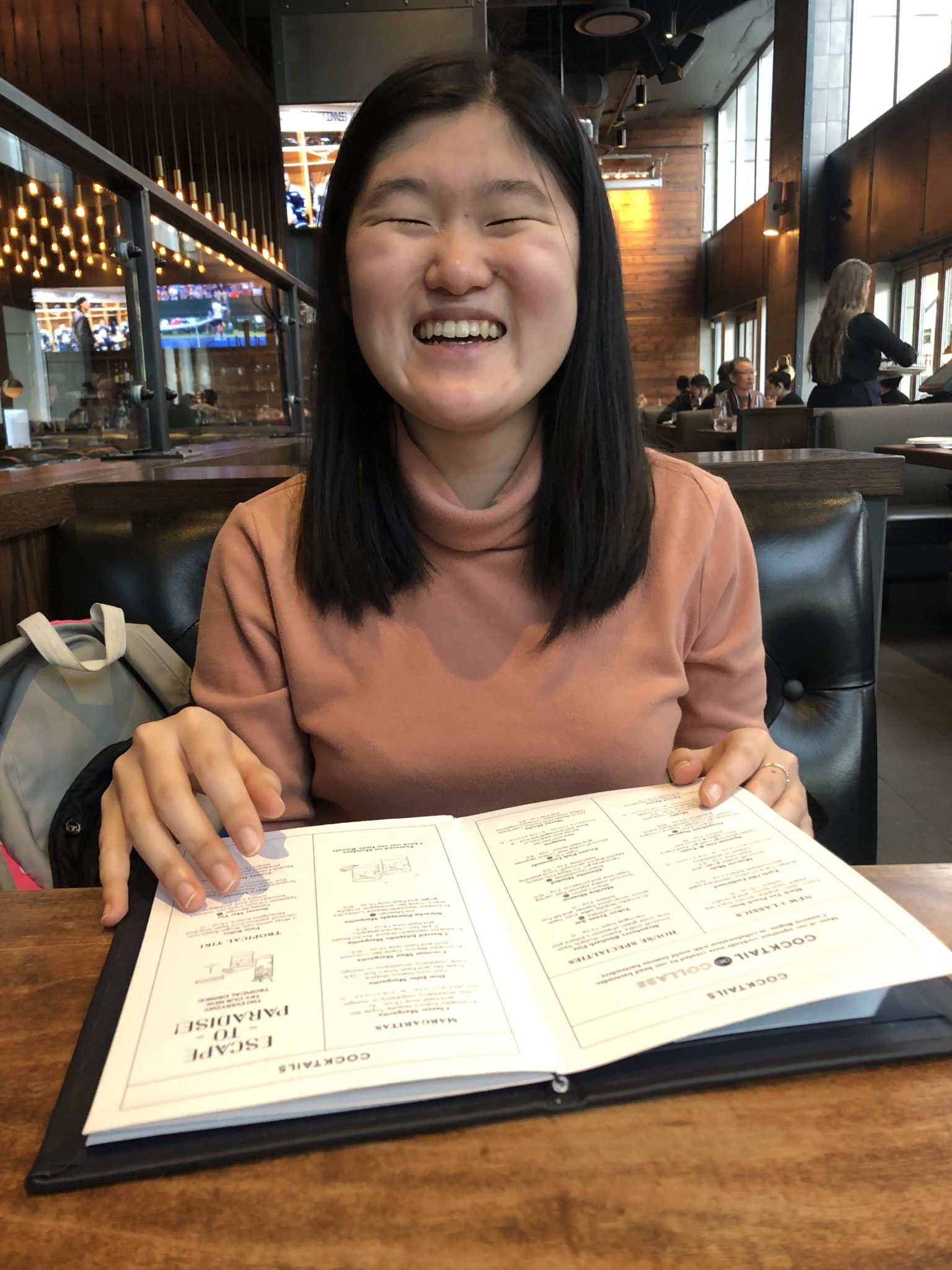 A person smiling widely while holding a menu